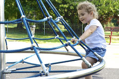 Young child on a swing roundabout at the playgroun Royalty Free Stock Photography