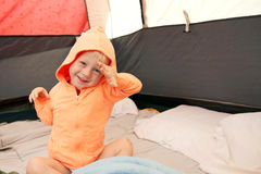 Young Child Waking up in Tent after Camping. A happy young boy child is waking up in a tent after spending the night camping stock images