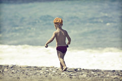 Young child walking on the beach Royalty Free Stock Photo