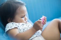 Young child watch tv on a smartphone. Young girl is slouched on a couch while watching tv on a cellphone royalty free stock photography