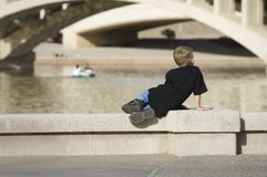Young child watching others at play. A young child observes others boating on an inner city waterway Stock Photos