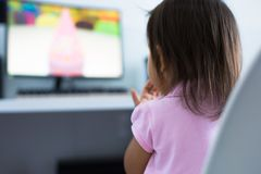 Young child watching tv on the computer at home stock photos