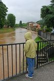 Young child with waterproof watch with dismay the growing river. High level stock photos