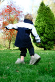 A young child wearing his father's shoes. And learning how to walk in them. Concept : Growth and development Royalty Free Stock Photos