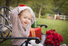 Young Child Wearing Santa Hat Sitting with Christmas Gifts Outsi Royalty Free Stock Images