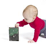 Young child in white background with hard drive. Red shirt and blue trousers Stock Photography
