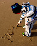 Young Child writing Dad in the sand Stock Image
