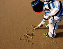 Young Child writing Dad in the sand Royalty Free Stock Photos