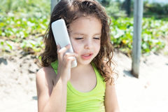 Young child in a yellow shirt speaking at phone. Outside in a park with green plants in the background Royalty Free Stock Photo