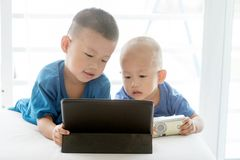 Children addicted to tablet. Young children addicted to technology gadget. Asian boys playing with digital tablet pc at home royalty free stock photography
