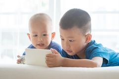 Kids addicted to smart phone. Young children addicted to technology gadget. Asian boys playing game with smart phone at home royalty free stock images