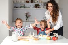 Young children bake cake with their mother in the kitchen at hom. E stock photo