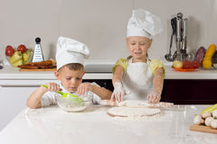 Young children baking homemade pizzas. Rolling out dough for the base at a kitchen counter in their white aprons and chefs hats stock photo