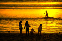 Young Children at Beach. Young Children Playing on the Beach at Sunset Stock Images