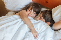 Young children - boy and girls - sleeping in bed at home, indoor Stock Images