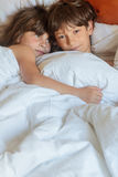 Young children - boy and girls - sleeping in bed at home, indoor Royalty Free Stock Image
