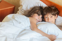 Young children - boy and girls - sleeping in bed at home, indoor Royalty Free Stock Images