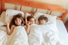 Young children - boy and girls - sleeping in bed at home, indoor Stock Photos