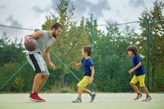 Young children, brothers and their father, playing basketball Royalty Free Stock Images
