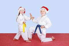 Young children in caps Santa Claus coach exercise karate Royalty Free Stock Photography