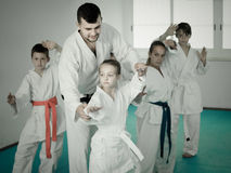 Young children doing karate kicks with male coach. During karate class Royalty Free Stock Image
