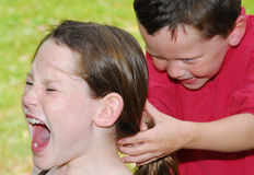 Young children fighting. And bullying on playground Stock Photo