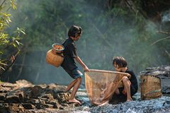 Young children with friend fishing in the river at countryside. Stock Images