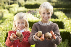 Young children in garden pose with vegetables Stock Photography