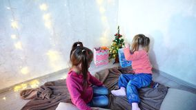 Young children of girls laugh and fool around, sitting on floor and on rug, against background of wall with garland and. Little girls smile and pose in camera stock video footage