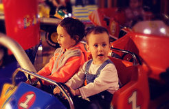 Young children go to a small car. Little girl and boy ride on the carousel Stock Image