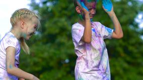 Young children having fun and throwing colorful holy powder at each other