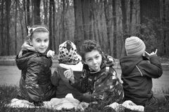 Young children indulge in a clearing. Four small children indulge in the meadow, show language grimace royalty free stock photo