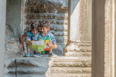 Young children looking at tourist map in Angkor wat, cambodi Stock Image