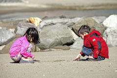YOUNG CHILDREN PLAY ON THE BEACH IN WINTER Royalty Free Stock Images