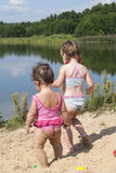 Young children playing on the beach near the lake. Royalty Free Stock Image