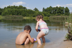 Young children playing on the beach near the lake. Royalty Free Stock Images