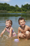 Young children playing on the beach near the lake. Stock Photo