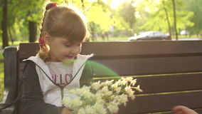 Young children playing with a flower in the Park. Little girl and little boy playing with a inflorescence of a chestnut sitting on a Park bench at sunset stock video