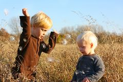 Young Children Playing Outside in Autumn. Two young children, a little boy and his baby brother, are playing outside in the country throwing fuzzy milkweed seeds Royalty Free Stock Photography