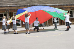 Young children playing with a parachute. In a playground Stock Photo