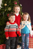 Young Children With Presents In Front Of Tree. Group Of Young Children With Presents In Front Of Christmas Tree Stock Photos