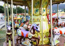 Young children ride on the carousel horse stock photography