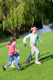 Young children running in park. Young children having fun playing chase in the park on a lovely summer's afternoon stock photography