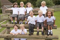 Young children sitting on benches and yelling Stock Image