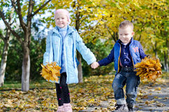 Young children skipping hand in hand. While out in the park collecting colourful yellow autumn leaves together Royalty Free Stock Image