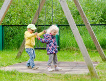 Young children swinging on a swing Royalty Free Stock Photos