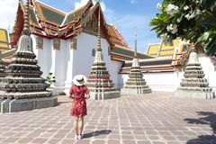 Young Chinese or Asian woman is traveling and sightseeing inside Wat Pho temple in Bangkok. Thailand royalty free stock photography