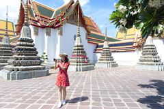 Young Chinese or Asian woman is traveling and sightseeing inside Wat Pho temple in Bangkok. Thailand stock photo