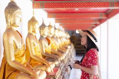 Young Chinese or Asian woman is traveling and sightseeing inside Wat Pho temple in Bangkok. Thailand royalty free stock images