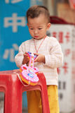 Young Chinese boy playing with his plastic toy, Guangzhou, China